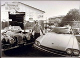 Nick Manarello with two Jaguar automobiles at his auto service garage, 1986